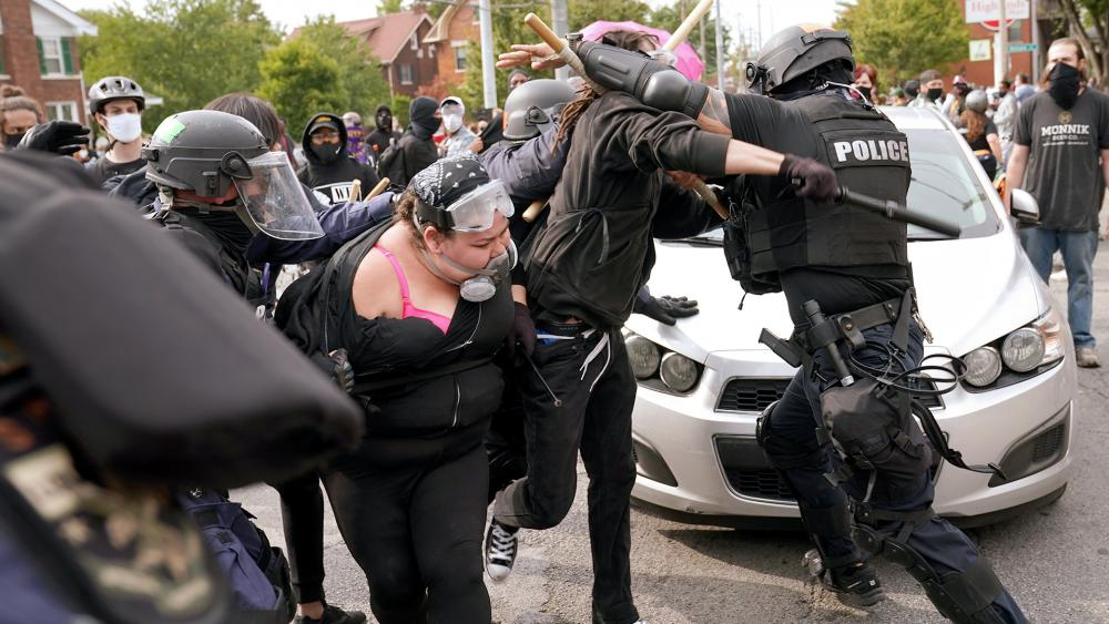 Police and protesters clash, Wednesday, Sept. 23, 2020, in Louisville, Ky. A grand jury has indicted one officer on criminal charges six months after Breonna Taylor was fatally shot by police in Kentucky. (AP Photo/John Minchillo)