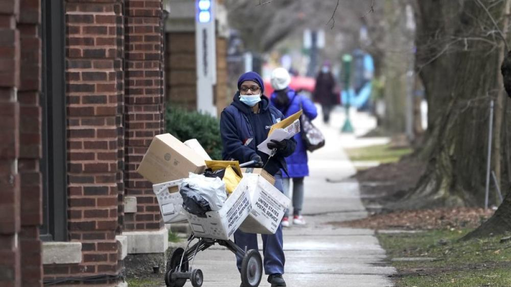 A U.S. postal worker delivers packages, boxes and letters Tuesday, Dec. 22, 2020, along her route in the Hyde Park neighborhood of Chicago. (AP Photo/Charles Rex Arbogast)