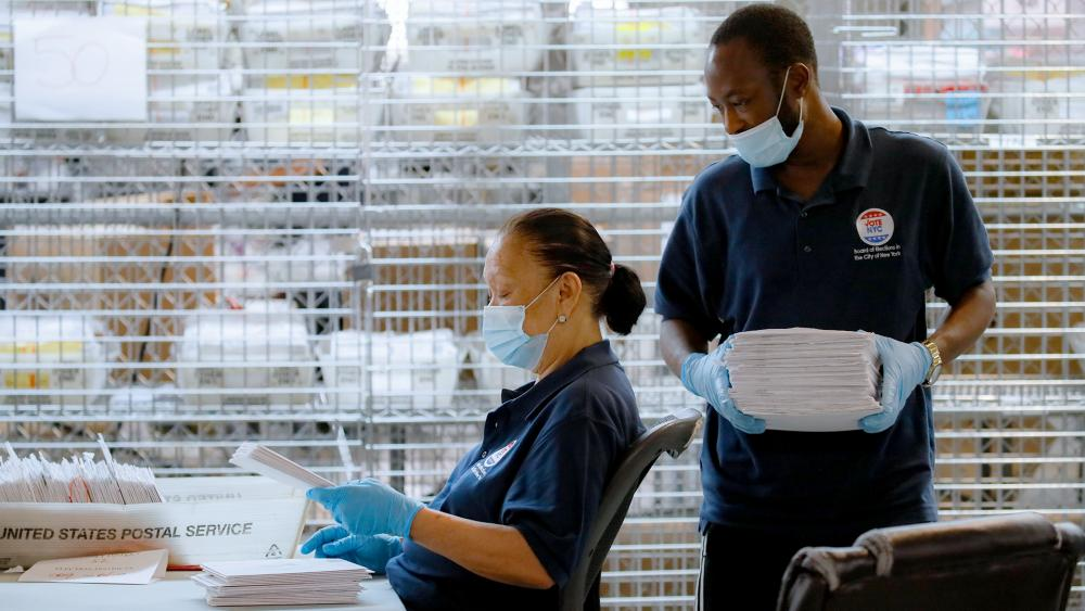 Workers wear personal protective equipment as they check ballots beside security cages at a Board of Elections facility, Wednesday, July 22, 2020, in New York. (AP Photo/John Minchillo)