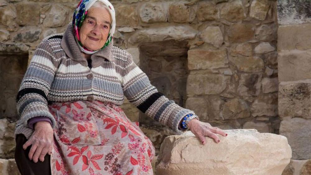Margalit Zinati and the ancient stone, Photo, Ritvo, courtesy of Beit Zinati