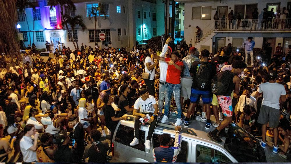 Crowds defiantly gather in the street while a speaker blasts music an hour past curfew in Miami Beach, Fla., on Sunday, March 21, 2021. (Daniel A. Varela/Miami Herald via AP)
