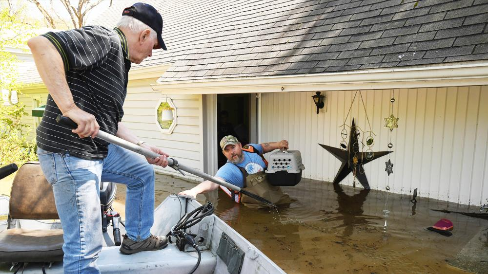 Don Thomas of Saginaw pulls his boat up to his son Jason Thomas who went back to his house near W. Signet in Midland to retrieve his family's cats. Flooding along the Tittabawassee River in Mich. on May 20, 2020. (Daniel Mears/ The Detroit News via AP)