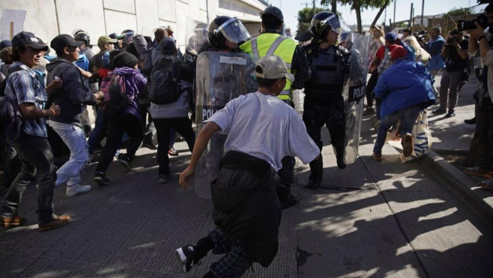 Migrants break past a line of police as they run toward the Chaparral border crossing in Tijuana, Mexico, Sunday, Nov. 25, 2018, near the San Ysidro entry point into the U.S. AP photo.