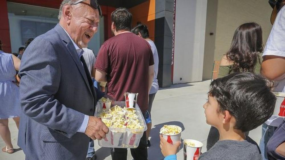 Larry Porricelli, vice president of Maya Cinemas, walks through the crowd of guests to pass out popcorn to theatergoers attending the first movies at the Maya Cinemas Theater in Delano, Calif.