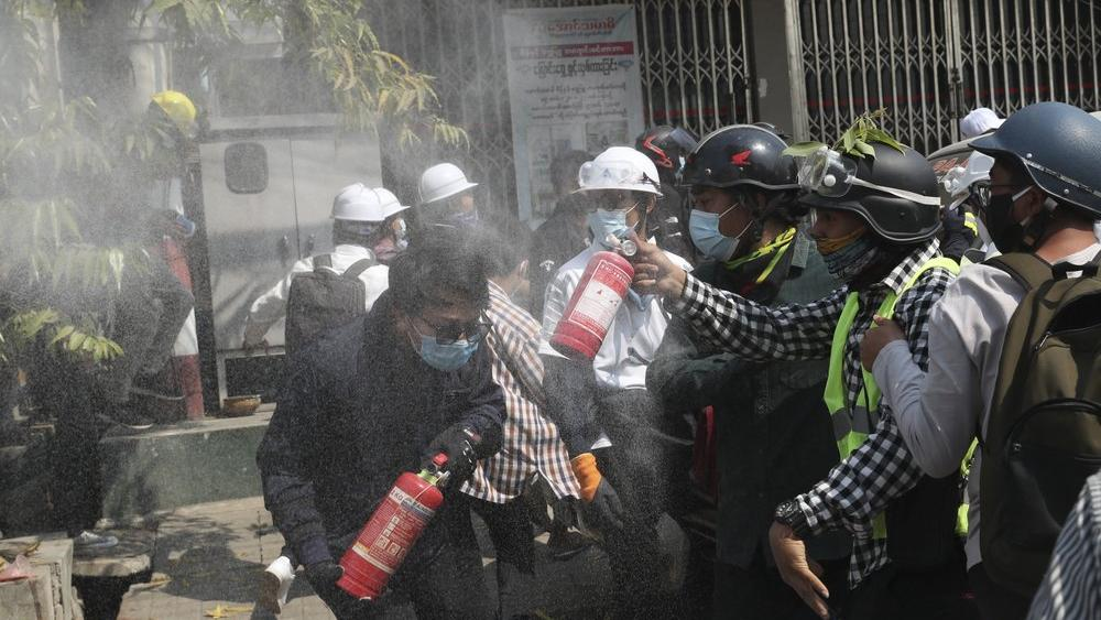 Anti-coup protesters discharge fire extinguishers, tear gas fired by police in Mandalay, Myanmar, Sunday, March 7, 2021. (AP Photo)