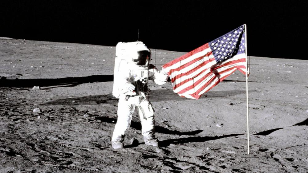 """Charles """"Pete"""" Conrad Jr., the third human to walk on the moon on the Apollo 12 mission, stands with the U.S. flag on the lunar surface. (Image courtesy: NASA)"""