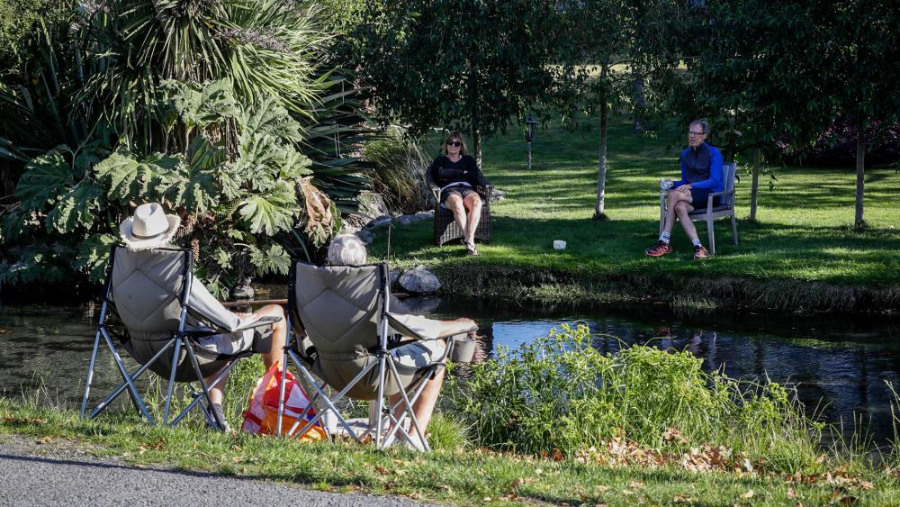 Neighbors chat across a stream as they practice social distancing in a suburb of Christchurch, New Zealand, April 5, 2020. (AP Photo/Mark Baker)