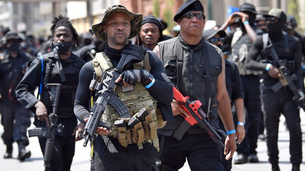 """Armed members of the """"NFAC"""" march through Louisville, KY, on July 25, 2020 to demand justice for Breonna Taylor (AP Photo/Timothy D. Easley)"""