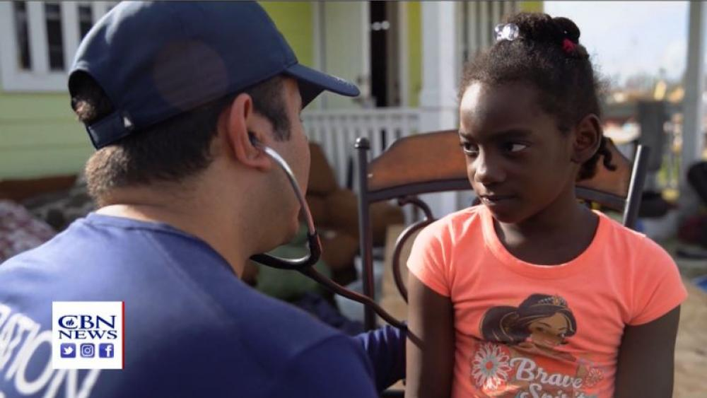 An Operation Blessing doctor checks the health of a young resident. (Image credit: CBN News)