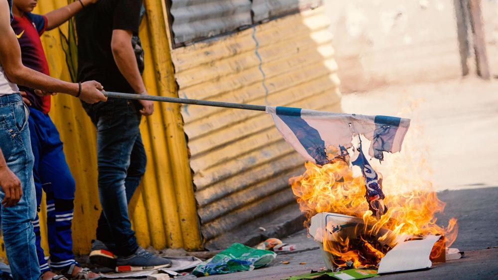 Palestinians burn Israeli flag