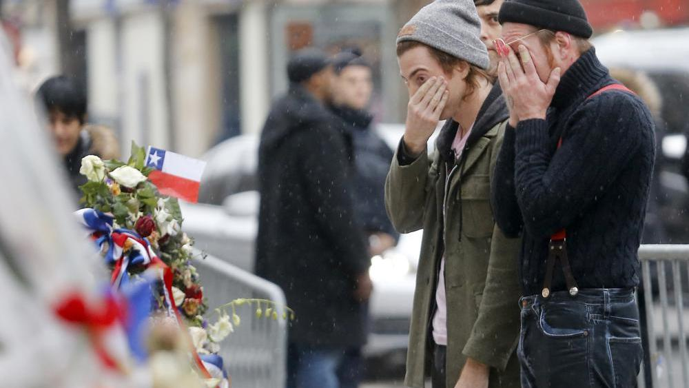 In this Dec.8, 2015 file photo, people pay their respects to the victims who died in a Nov. 13 attack, at the Bataclan concert hall in Paris. (AP Photo/Jacques Brinon, File)