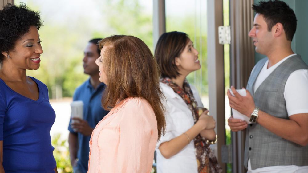 People greet one another in a church lobby. (Image credit: Adobe Stock)