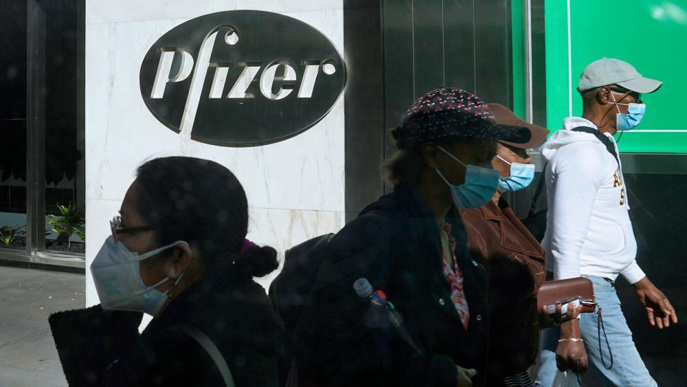 Pedestrians walk past Pfizer world headquarters in New York on Monday Nov. 9, 2020. (AP Photo/Bebeto Matthews)