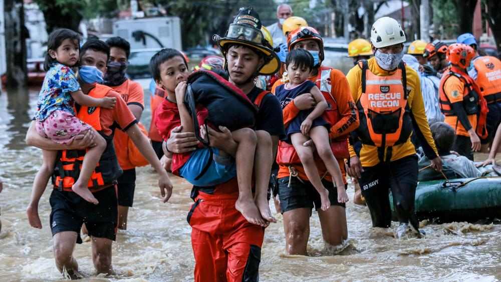 Rescuers carry children out from a flooded street due to heavy rains brought by Typhoon Vamco in Marikina City, east of Manila, Philippines, Nov. 12, 2020. (AP Photo/Basilio Sepe)