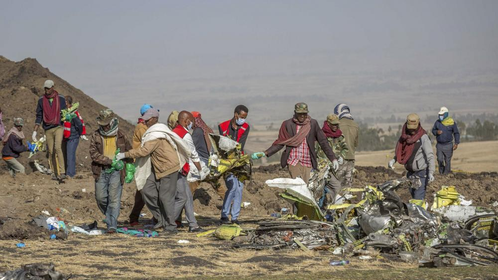 Workers gather at the scene of an Ethiopian Airlines flight crash near Bishoftu, or Debre Zeit, south of Addis Ababa, Ethiopia, Monday, March 11, 2019. (AP Photo/Mulugeta Ayene)