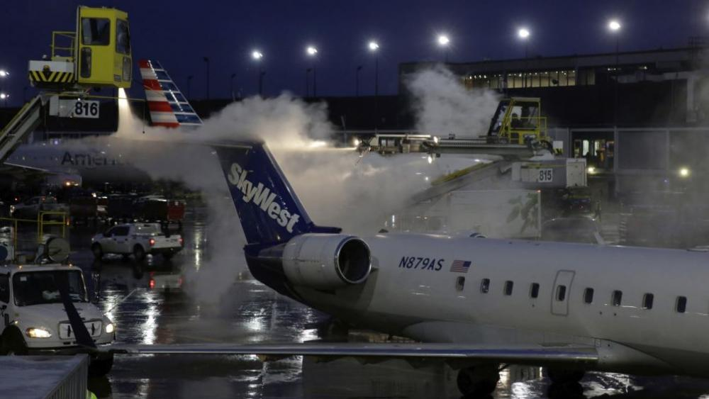 A deicing agent is applied to a SkyWest airplane before its takeoff, Friday, Jan. 18, 2019, at O'Hare International Airport in Chicago. (AP Photo/Kiichiro Sato)