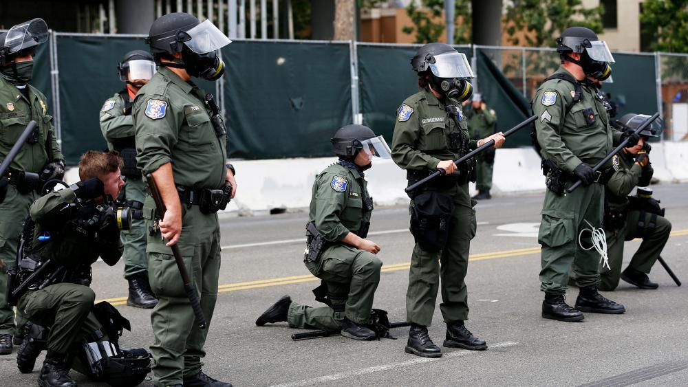 Santa Clara Sheriff's officers take a knee during peaceful protest in San Jose, Calif., Sunday, May 31, 2020 (AP Photo/Josie Lepe)