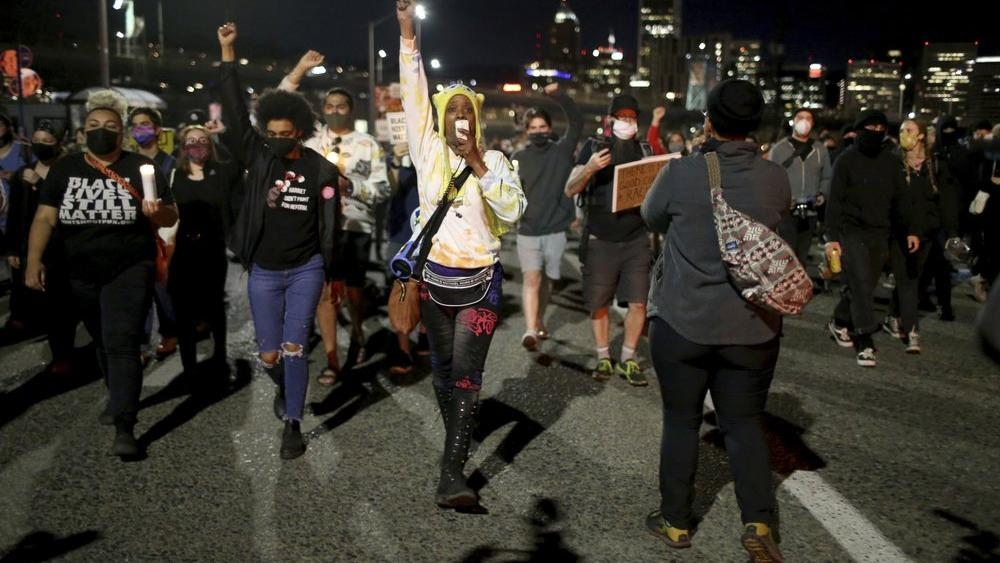 A group marches on Friday, April 16, 2021, in Portland, Ore. (Dave Killen/The Oregonian via AP)