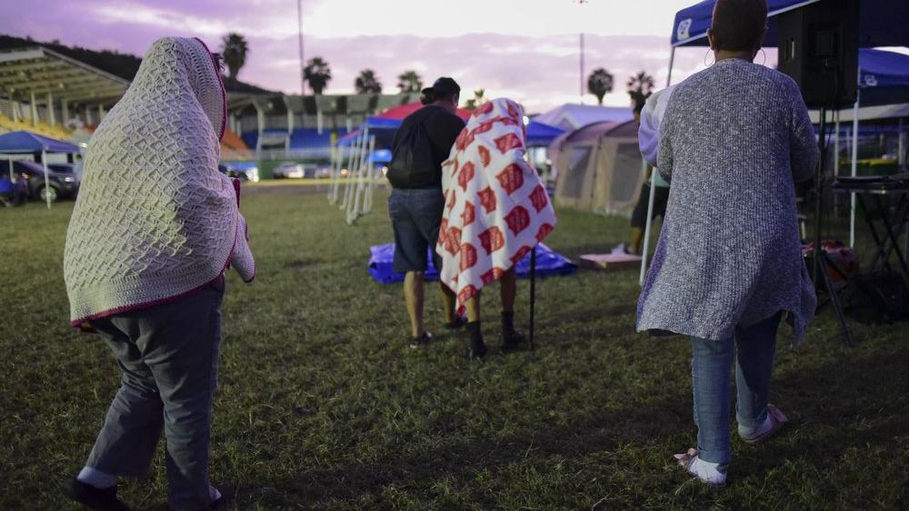 People get up after spending the night in a baseball stadium amid aftershocks and without electricity after the 6.4 magnitude earthquake in Guayanilla, Puerto Rico, at sunrise Friday, Jan. 10, 2020. (AP Photo/Carlos Giusti)