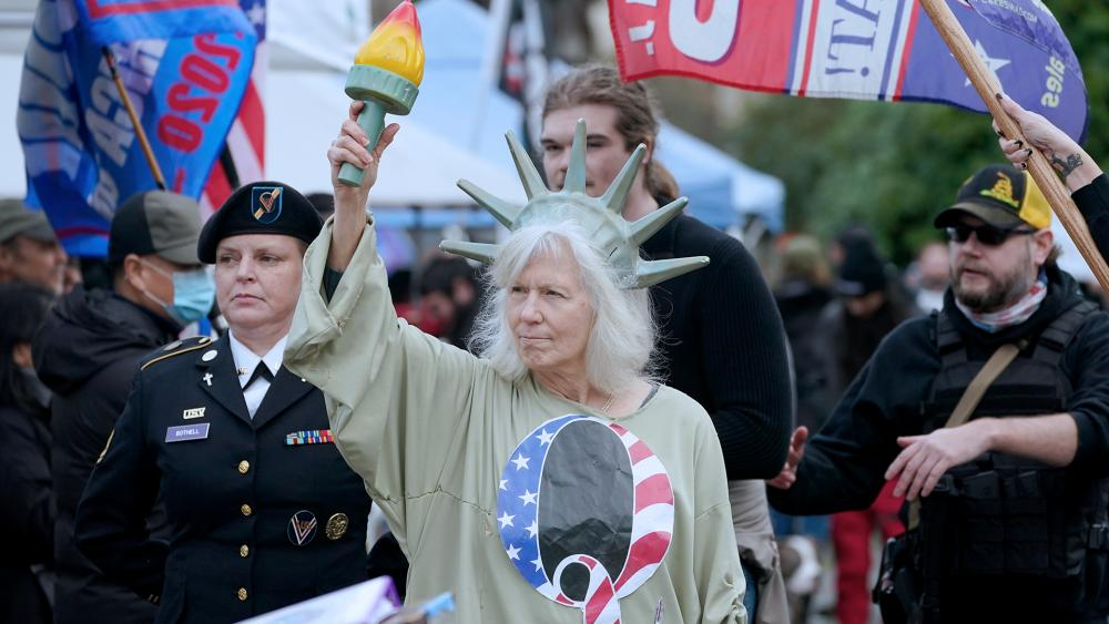 A person dressed as Lady Liberty wears a shirt with the letter Q, referring to QAnon, at a protest, Jan. 6, 2021, at the Capitol in Olympia, Wash. (AP Photo/Ted S. Warren)