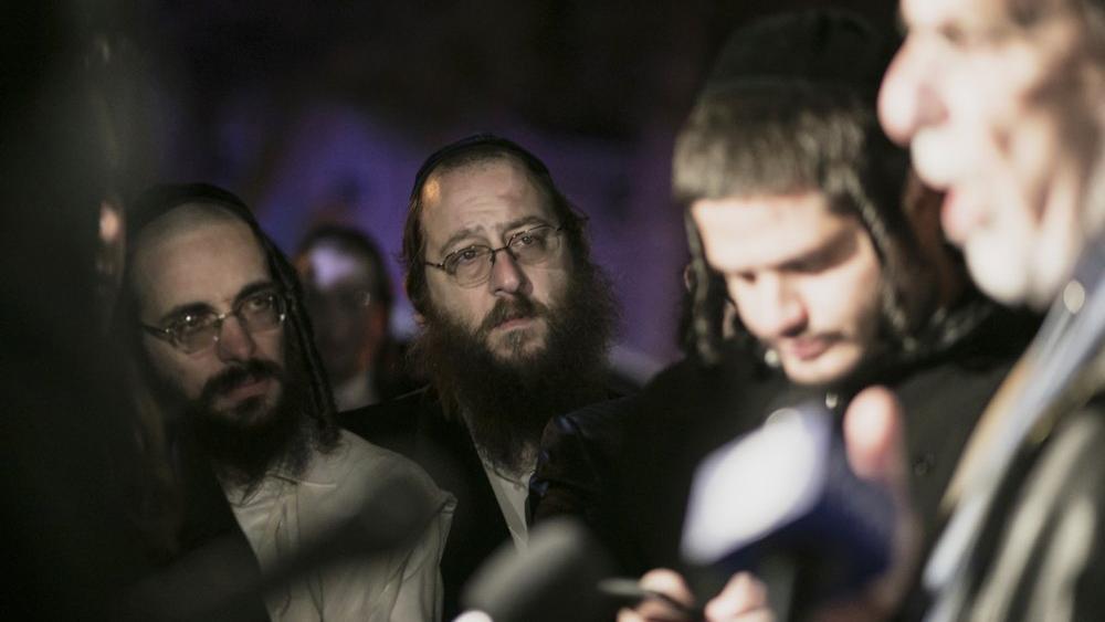 Orthodox Jewish people listen to N.Y. state Assemblyman Dov Hikind speak in Monsey, N.Y., Sunday, Dec. 29, 2019, following a stabbing late Saturday during a Hanukkah celebration. (AP Photo/Allyse Pulliam)