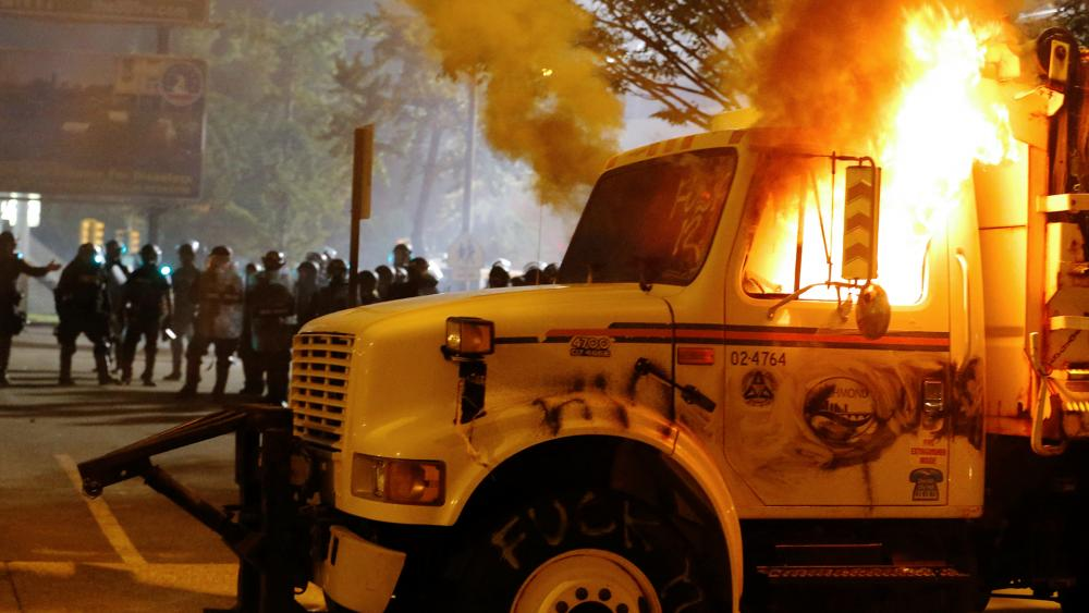 Police stand in front of a utility vehicle that was set on fire by protesters during a demonstration outside the Richmond Police Department headquarters on Grace Street in Richmond, Va., July 25, 2020 (Joe Mahoney/Richmond Times-Dispatch via AP)