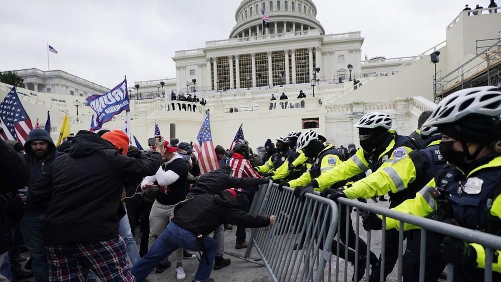 People try to break through a police barrier, Wednesday, Jan. 6, 2021, at the Capitol in Washington (AP Photo/Julio Cortez)