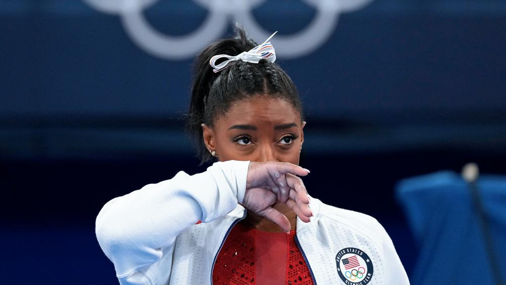 US gymnastic star Simone Biles watches gymnasts perform after an apparent injury, at the 2020 Summer Olympics, Tuesday, July 27, 2021, in Tokyo. Biles withdrew from the team finals. (AP Photo/Ashley Landis)