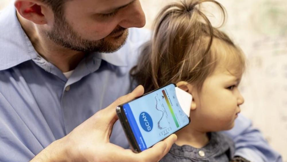 Dr. Randall Bly uses a uses a phone app and a paper funnel to focus the sound, to check his daughter for an ear infection, at the UW School of Medicine in Seattle. (Dennis Wise/University of Washington via AP)