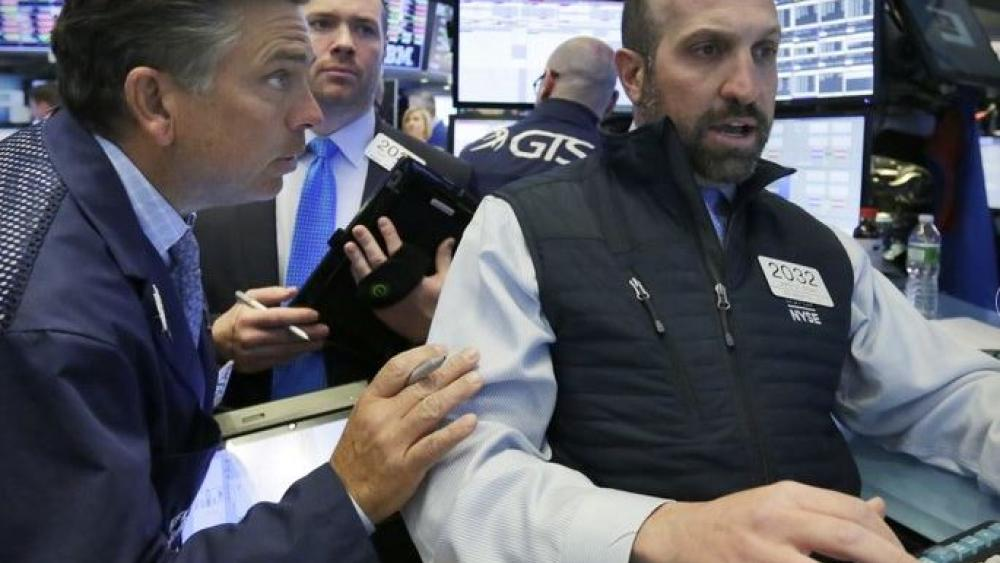 Specialist James Denario, right, works with traders on the floor of the New York Stock Exchange. (AP Photo)