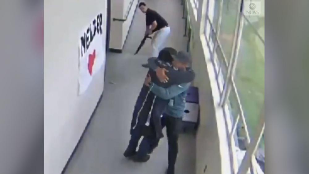 In this screenshot from school surveillance video, a Portland, Oregon high school coach embraces a student he has just disarmed. (Image credit: ABC News)
