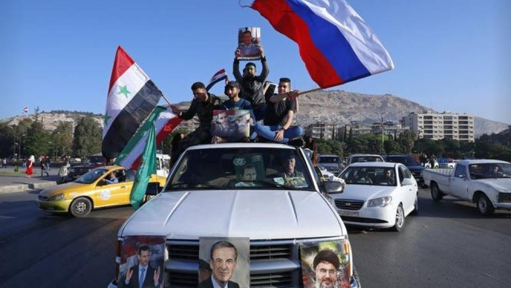 Syrian government supporters wave Syrian, Iranian and Russian flags in a demonstration Saturday morning.