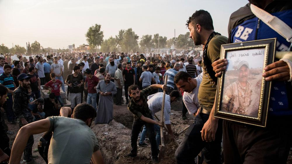Syrians bury Syrian Democratic Forces fighters killed fighting Turkish advance in the Syrian town of Qamishli, Oct. 12, 2019. Turkey's military says it has captured a key Syrian border town Ras al-Ayn under heavy bombardment. (AP Photo/Baderkhan Ahmad)