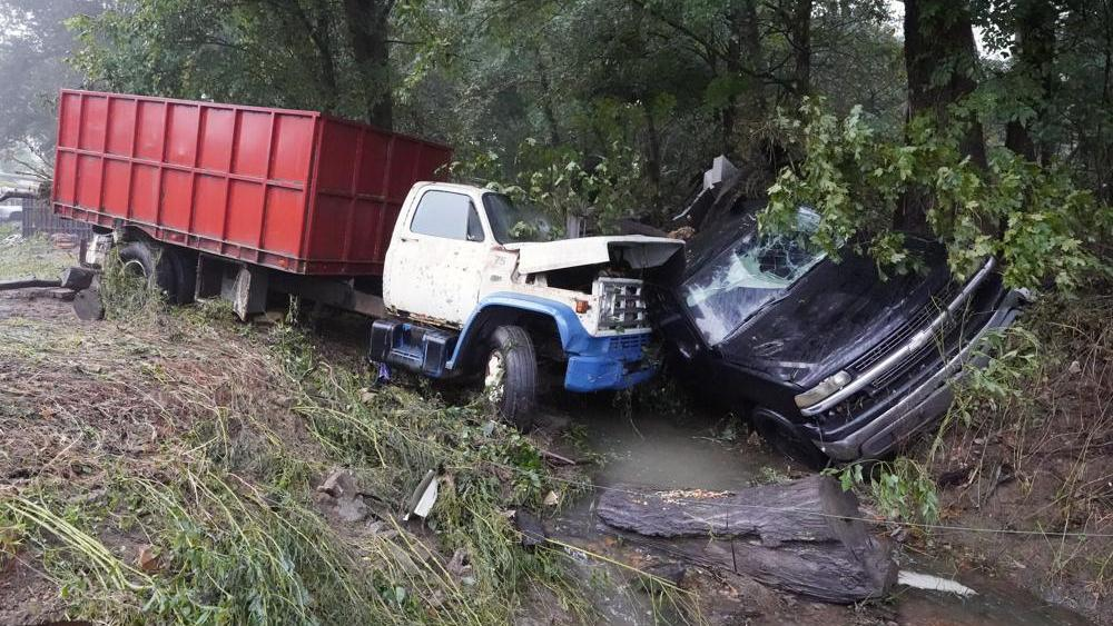 A truck and a car sit in a creek Sunday, Aug. 22, 2021, after they were washed away the day before in McEwen, Tenn. (AP Photo/Mark Humphrey)