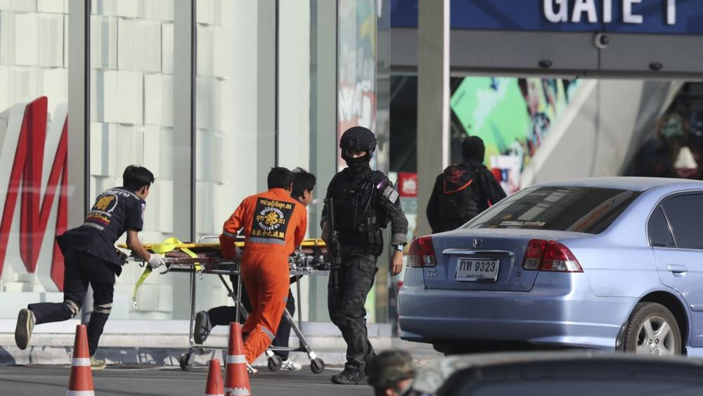 Medics carry a stretcher towards Terminal 21 Korat mall as commando soldiers work the scene of a shooting at the mall in Nakhon Ratchasima, Thailand, Sunday, Feb. 9, 2020.