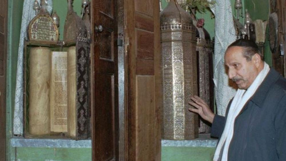 In this AP file photo from January, 2000, Youssef Jajati, a Jewish community leader in Syria, points out the Torah holy book preserved in a silver container in Joubar's Synagogue which dates to 718 BC.