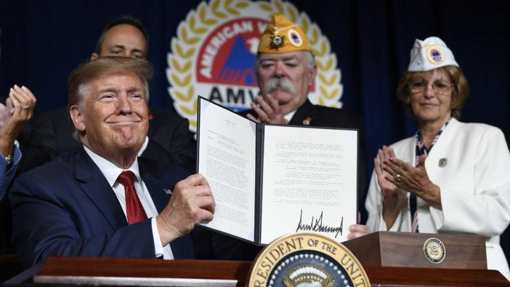 President Donald Trump holds up a presidential memorandum that he signed that discharges the federal student loan debt of totally and permanently disabled veterans. (AP Photo/Susan Walsh)