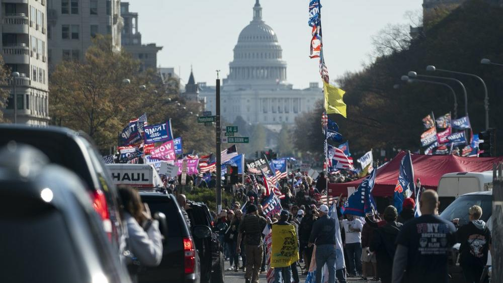 A motorcade carrying President Donald Trump drives by a group of supporters participating in a rally near the White House, Saturday, Nov. 14, 2020, in Washington. (AP Photo/Evan Vucci)