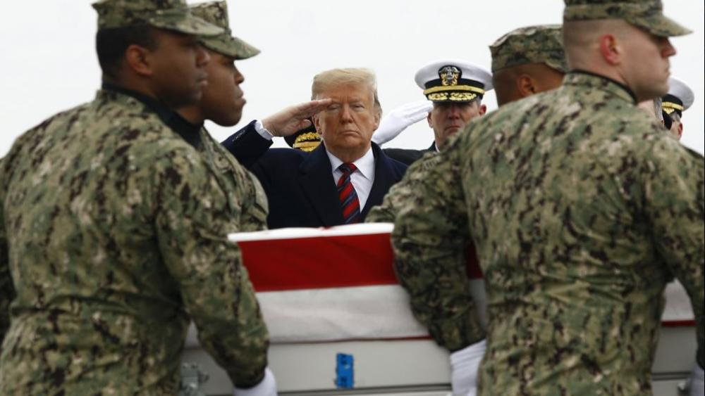 President Donald Trump salutes as a U.S. Navy carry team moves a transfer case containing the remains of Scott A. Wirtz, Saturday, Jan. 19, 2019, at Dover Air Force Base, Del. (AP Photo/Patrick Semansky)