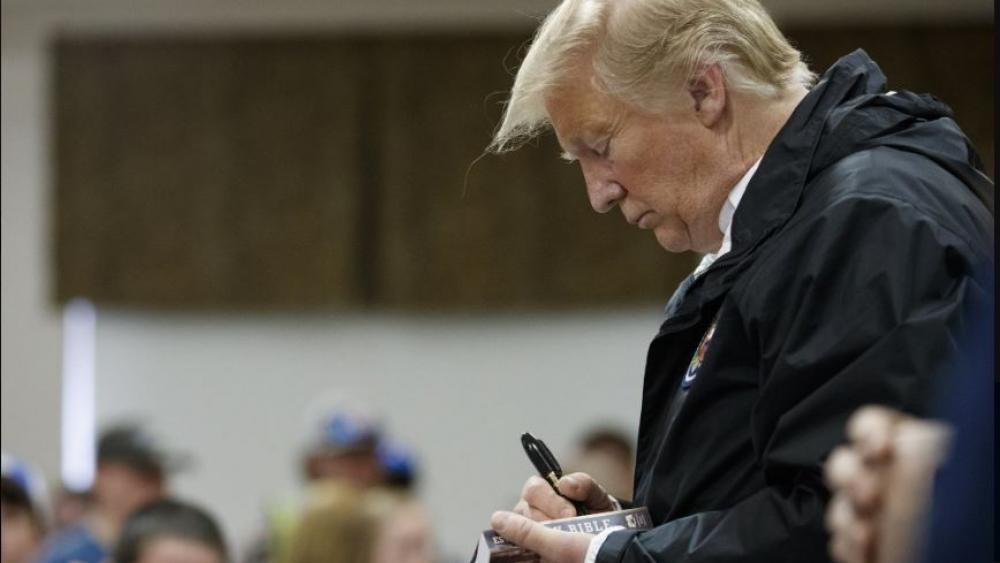 President Donald Trump signs a Bible as he greets people at Providence Baptist Church in Smiths Station, Ala., Friday, March 8, 2019, during a tour of areas where tornados killed 23 people in Lee County, Ala. (AP Photo/Carolyn Kaster)