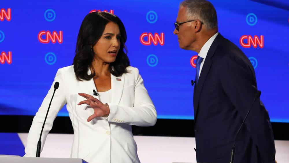 Rep. Tulsi Gabbard, D-Hawaii, and Washington Gov. Jay Inslee chat during a break in the second of two Democratic presidential primary debates hosted by CNN Wednesday, July 31, 2019, in the Fox Theatre in Detroit. (AP Photo/Paul Sancya)