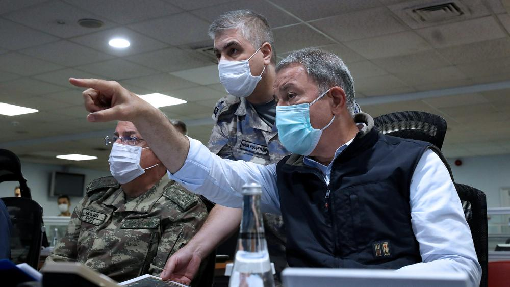 AP: Turkish Defense Minister Hulusi Akar, right, and army commanders wearing face masks to protect against the coronavirus, speak at a military headquarter, in Ankara, Turkey.