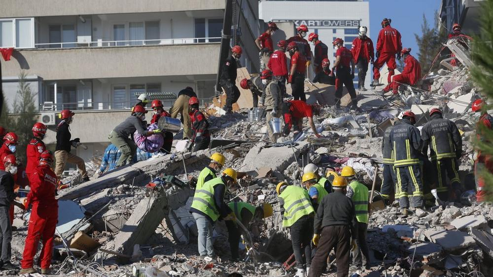 Members of rescue services search for survivors in the debris of a collapsed building in Izmir, Turkey, Saturday, Oct. 31, 2020. (AP Photo/Darko Bandic)