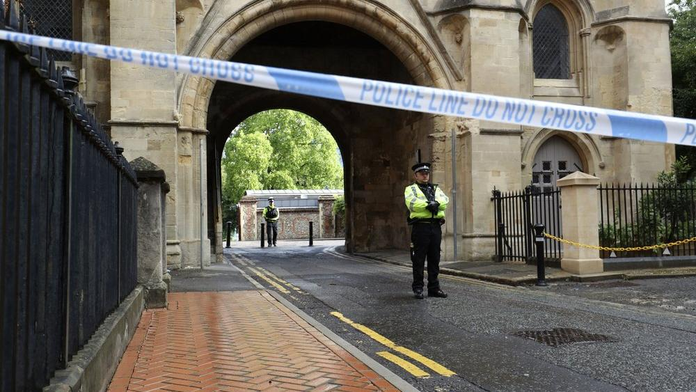 Police stand guard at the Abbey gateway of Forbury Gardens park in Reading town centre following Saturday's stabbing attack in the gardens (Jonathan Brady/PA via AP)