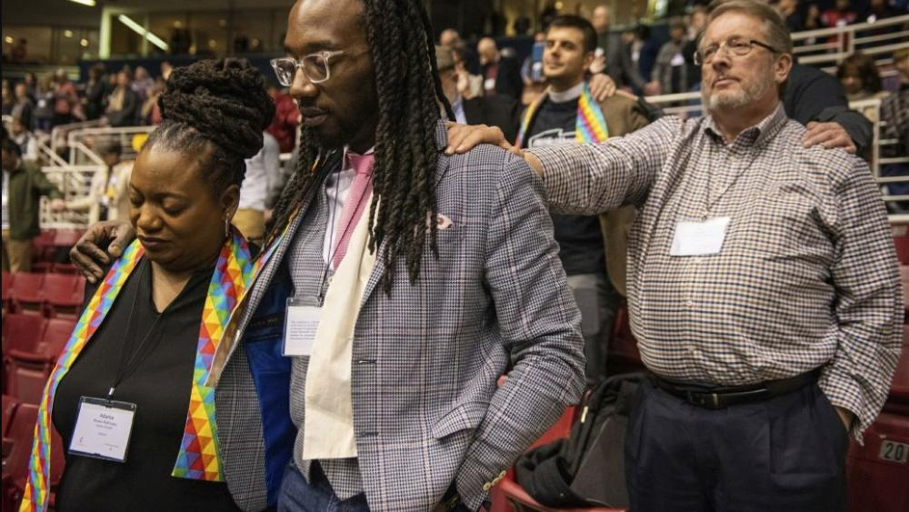 Adama Brown-Hathasway, left, The Rev. Dr. Jay Williams, both from Boston, and Ric Holladay of Kentucky join in prayer during the 2019 Special Session of the General Conference of The United Methodist Church in St. Louis, Mo. (AP Photo/Sid Hastings)