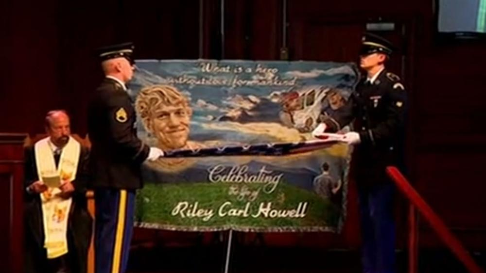A military honor guard folds the American flag in front of an image of Riley Howell at his funeral Sunday. (Screenshot credit: APTN)