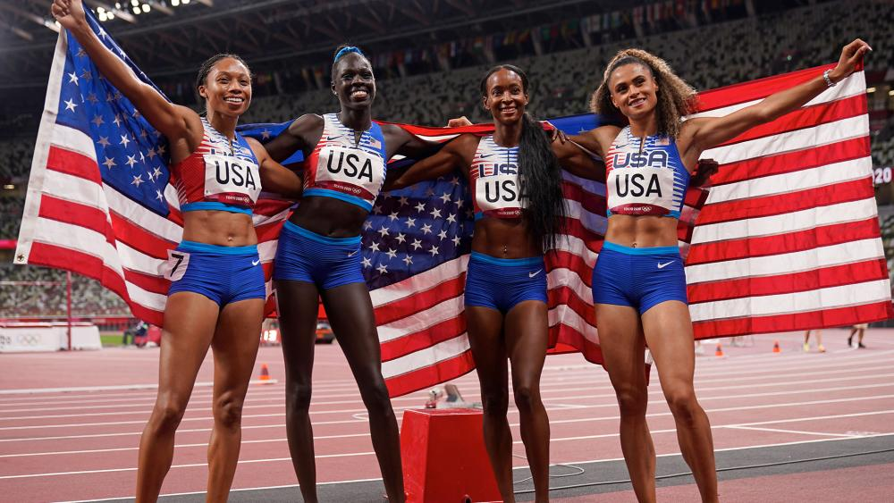 US runners Allyson Felix, Athing Mu, Dalilah Muhammad and Sydney Mclaughlin celebrate winning the gold in the women's 4 x 400-meter relay at the 2020 Summer Olympics (AP Photo/Charlie Riedel)