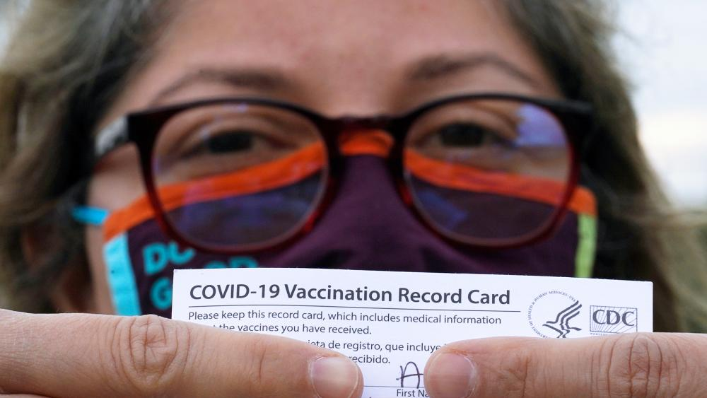 A woman poses with her vaccination card after getting her second Moderna COVID-19 shot  (AP Photo/David J. Phillip)