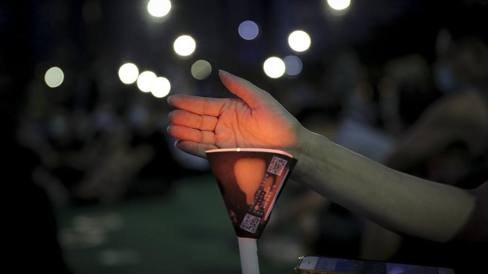 An activist holds a candle during a vigil for the victims of the 1989 Tiananmen Square Massacre (AP Photo/Kin Cheung)