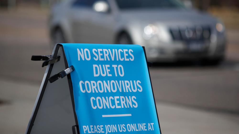 A sign stands outside a church to advise parishoners that services were cancelled because of the coronavirus pandemic Sunday, March 15, 2020, in Highlands Ranch, Colo. (AP Photo/David Zalubowski)